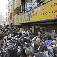 End of story: The media converge on a manga cafe where Aum Shinrikyo fugitive Katsuya Takahashi was seized by Tokyo police Friday morning, after 17 years on the run. Below: Takahashi is transferred to Metropolitan Police Department headquarters. | KYODO PHOTOS