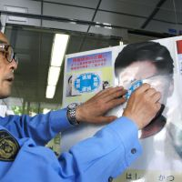 Done running: The deputy commissioner of Tokyo's Kamata police station places a sticker saying 'arrested' on the photo of Aum fugitive Katsuya Takashi after his capture Friday morning. | KYODO PHOTOS