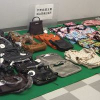 Came at a price: Counterfeit brand-name bags are lined up in July 2007, when Kobe Customs officials charged Japanese nationals who attempted to smuggle the fake goods after coming back to Okayama airport from China. | COURTESY OF JAPAN CUSTOMS