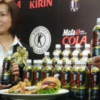 Hip pop: Kirin Beverage Co. employees show Mets Cola during a press review March 26. The cola debuted April 24, bearing a tokuho mark (below). | KYODO / YOSHIAKI MIURA