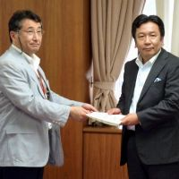 Through the motions: Junji Annen, chairman of the trade and industry ministry panel scrutinizing Tokyo Electric Power Co.'s rate hike request, hands a report to his boss Yukio Edano on July 5. | KYODO