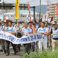 Consequences: Protesters march around a U.S. base in Sasebo, Nagasaki Prefecture, to oppose a plan to deploy the Osprey to Okinawa.