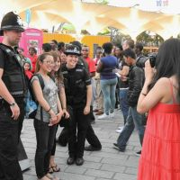 Only show in town: Tourists snap shots with bobbies in London on July 27. Despite the lure of the Olympics, soaring hotel prices and traffic restrictions have seen the number of Japanese tour groups to the Lake District and other tourism destinations plummet. | KYODO
