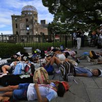 Ground zero: Students feigning death lie on the ground in front of the A-Bomb Dome on the 67th anniversary of the atomic bombing of Hiroshima on Monday. | KYODO PHOTOS