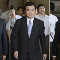 Between a rock: Koriki Jojima (center), Diet affairs chief of the ruling Democratic Party of Japan, walks in the Diet on Wednesday as he continues negotiations over possible dissolution of the Lower House with his counterparts Fumio Kishida (right) of the Liberal Democratic Party and Yoshio Urushibara of New Komeito. | KYODO