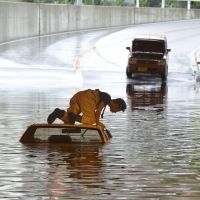 Done driving: A man looks into his flooded car  Tuesday in Neyagawa, Osaka Prefecture. | KYODO