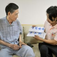 Common language: A staff member at a facility for the elderly in Kobe uses vocabulary cards last month to communicate with He Zhaolin, a Vietnamese man of Chinese descent. | KYODO