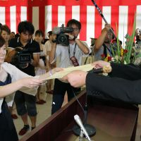 New chapter: Shoko Kubota receives her certificate from Kawauchi Mayor Yuko Endo at a coming-of-age day ceremony in the Fukushima Prefecture village on Tuesday. | KYODO