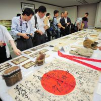 Another time: People in Seoul on Monday view personal effects and documents that belonged to Koreans who were forced into working for the Japanese during the colonial period. | KYODO