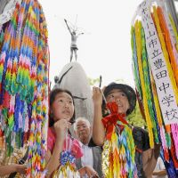 Continuing the legacy: Elementary school students bring paper cranes to the Children's Peace Monument in Hiroshima Peace Memorial Park. | KYODO