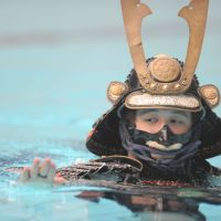 Samurai simmer: Mutsuo Koga shows his swimming skills while wearing traditional armor and a helmet in Yokohama on Aug. 19. | AFP-JIJI