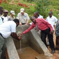 Tapping new ground: Local people and Zensho Holdings Co. employees run a water supply system June 4 in Chingwa, Rwanda, built with fair trade funds. Zensho buys fair trade coffee beans from Rwandan farmers for its restaurants in Japan. | ZENSHO HOLDINGS