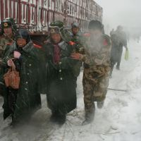 Snowbound: Drivers stranded in a snowstorm on a highway near the Great Wall outside Beijing are evacuated by police Monday. | KYODO