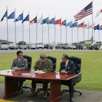 Evac pact: A pact is signed Monday at Camp Foster in Okinawa by (from left) Ginowan Mayor Atsushi Sakima, Maj. Gen. Peter Talleri and Chatan Mayor Masaharu Noguni to allow citizens of the prefecture to evacuate to U.S. military installations in times of natural disasters. | KYODO