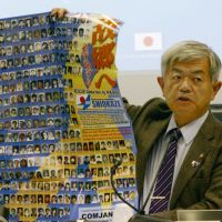 Open cases: Kazuhiro Araki, who heads a group probing Pyongyang's abductions of Japanese, holds a poster bearing photos of the missing Thursday during a symposium in Geneva. | KYODO
