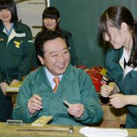 And they're off: A student at Tokyo Metropolitan Kogei High School teaches Prime Minister Yoshihiko Noda how to make a cellphone strap Saturday in Bunkyo Ward as jockeying for the Dec. 16 Lower House election kicked off. | KYODO