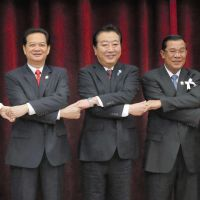 Common cause: Prime Minister Yoshihiko Noda (center) holds hands with his counterparts at the Association of Southeast Asian Nations summit meeting in Phnom Penh on Monday. | KYODO