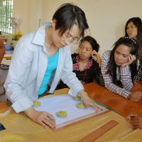 Teaching independence: Designer Yuko Sato teaches Cambodian children how to sew in August as part of a program arranged by NPO Kokkyo naki Kodomotachi (Children without Borders). | KYODO