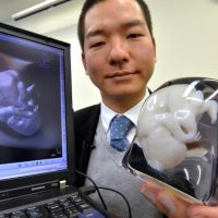 It's a fetus: Tomohiro Kinoshita of Fasotec Co. displays a 3-D acrylic resin model of a 9-month-old fetus and the ultrasound image used to produce it at the firm's Chiba headquarters Monday. Fasotec is offering the product to pregnant mothers for ¥100,000. | AFP-JIJI