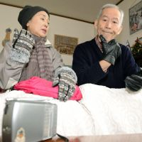 Cold comforts: Toshiko Yoshida and her husband, Minoru, listen to the radio Thursday at their home in Noboribetsu, Hokkaido, after the area suffered blackouts caused by snowstorms. | KYODO
