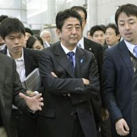 Hitting the airwaves: Reporters surround Shinzo Abe, the incoming prime minister, after he spoke on a television program Sunday in Minato Ward, Tokyo. | KYODO