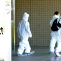 Fukushima foothold: Workers in protective suits leave Tokyo Electric Power Co.'s newly opened regional headquarters in Fukushima Prefecture on Friday at J Village in the town of Naraha. | KYODO
