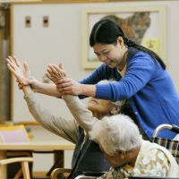 Foreign aid: Gina Konishi gets on-the-job training to become a caregiver at Shofuen, a nursing home for visually impaired elderly, in Ofunato, Iwate Prefecture, on Nov. 6. | KYODO