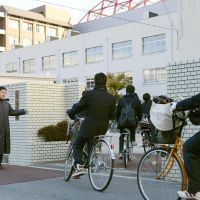 Under a cloud: Students arrive at Sakuranomiya Senior High School in the city of Osaka on Thursday morning. | KYODO