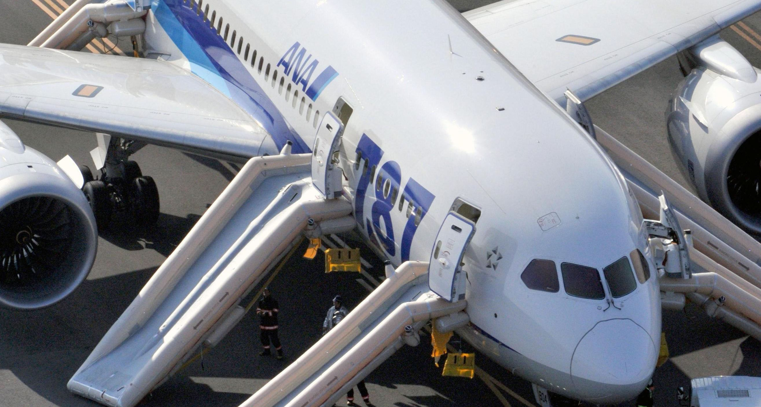 What went wrong?: Officials inspect an All Nippon Airways Boeing 787 after it made an emergency landing Wednesday at Takamatsu Airport in Kagawa Prefecture. Everyone aboard evacuated via emergency chutes. | KYODO