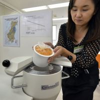 Removing the risk: An employee for the Becquerel Center, a firm that rents machines that check for radiation levels, demonstrates how to use a scintillator to measure radiation levels in a sample of mashed persimmon at its shop in Kashiwa, Chiba Prefecture, on Oct. 21, 2011. | AFP-JIJI