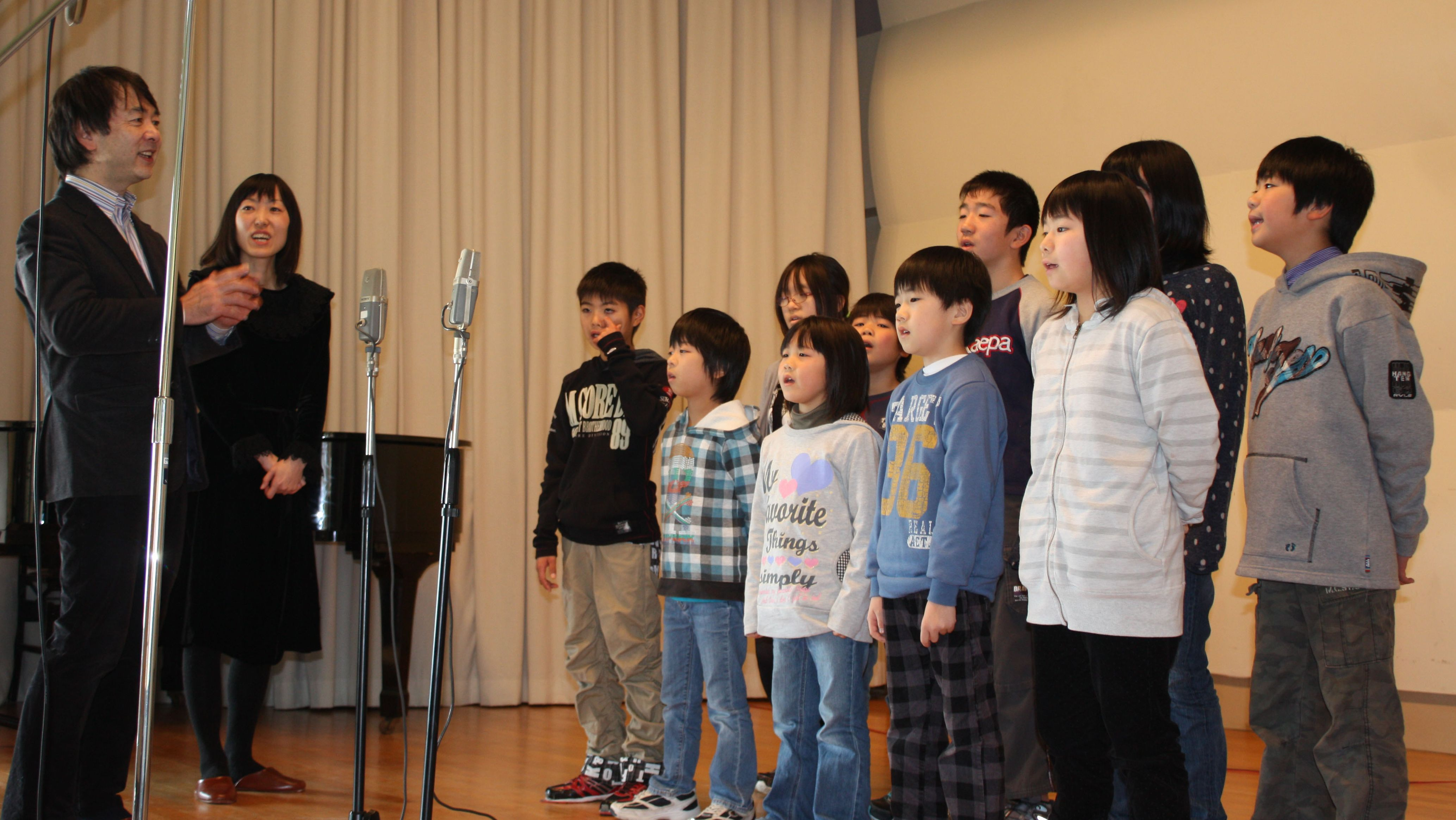 Preservation project: Jazz pianist Mitsuhiro Sakakibara (left) and violinist Satoko Sato direct the 10 pupils of Funakoshi Elementary School in Ishinomaki, Miyagi Prefecture, in December in the auditorium of an old high school where the school is temporarily housed. | SETSUKO KAMIYA