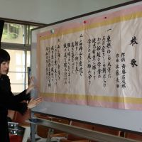 Sato stands next to a whiteboard on which the lyrics of Funakoshi's school song are posted for reference during the recording. | SETSUKO KAMIYA