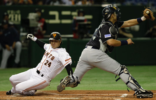 Continental drift: Yomiuri's Yoshinobu Takahashi slides home beside Seattle catcher Jesus Montero at Tokyo Dome on Monday night. | AP
