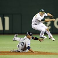 Double trouble: A's shortstop Cliff Pennington throws to complete a fifth-inning double play as the Mariners' Miguel Olivo slides on Tuesday. Seattle defeated Oakland 3-1 in 11 innings. | AP