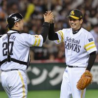 Swept away: Hawks pitcher Nagisa Arakaki and catcher Toru Hosokawa celebrate after defeating the Buffaloes 5-1 on Sunday in Fukuoka. | KYODO