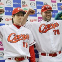 Show of strength: Nick Stavinoha (right) and Yusuke Nomura celebrate the Carp's victory over the Swallows on Sunday. | KYODO