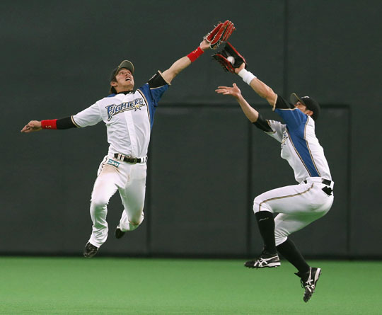 I got it: Fighters outfielders Yoshio Itoi (right) and Daikan Yoh go after a fly ball on Wednesday at Sapporo Dome. | KYODO