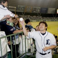 A moment to treasure: A young fan receives an autographed baseball from Lions pitcher Kazuhisa Ishii on Friday at Seibu Dome. | KYODO