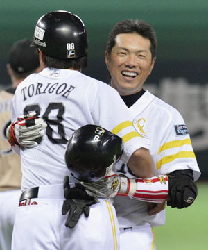 Milestone moment: Fukuoka Softbank's Hiroki Kokubo celebrates his 2,000th career hit with coach Yusuke Torigoe on Sunday. | KYODO