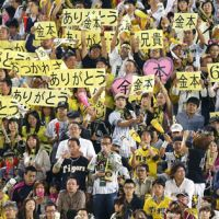 Heartfelt tribute: Hanshin Tigers fans hold up signs reading 'arigatou,' or thank you, and other symbols of support for longtime star Tomoaki Kanemoto, who played the final game of his 21-year career on Tuesday. Hanshin defeated the visiting Yokohama BayStars 3-0. | KYODO