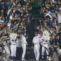 Pitcher Takayuki Kishi (left) and shortstop Hiroyuki Nakajima wave to the crowd after  the Lions' 8-0 win on Sunday at Seibu Dome. | KYODO