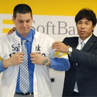 Ready to fly: Hawks manager Koji Akiyama helps new acquisition Bryan LaHair into his jersey on Wednesday in Fukuoka. | KYODO