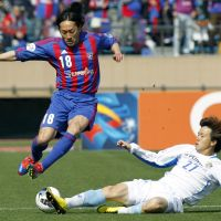 Collision avoidance: FC Tokyo's Naohiro Ishikawa jumps a tackle by Ulsan Hyundai's Kang Jin Ouk in Asian Champions League action at Tokyo's National Stadium on Tuesday. | AP