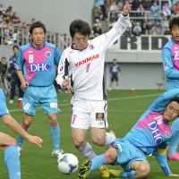Help wanted: Cerezo Osaka's Kim Bo Kyung (7) tries to dribble through the Sagan Tosu defense on Saturday. | KYODO