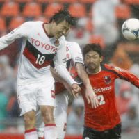 Drenched: Nagoya Grampus forward Kensuke Nagai (18) fires a header in the second half against Omiya Ardija at Nack5 Stadium on Saturday. The game ended in a 1-1 draw. | KYODO