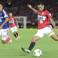 Attack mode: Urawa Reds player Tomoaki Makino prepares to kick the ball as Yuji Ono of Yokohama F. Marinos pursues him in Saturday's J.League match in Yokohama. Makino scored the go-ahead goal in Reds' 2-1 triumph. | KYODO