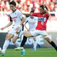 Singular focus: Keita Suzuki of the Urawa Reds tries to take the ball away from Cerezo Osaka's Kenyu Sugimoto during Saturday's J.League match in Saitama. | KYODO