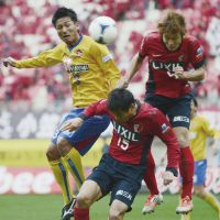 Stalemate: Vegalta's Atsushi Yanagisawa (left) vies for the ball with Kashima's Yuya Osako (right) and Takeshi Aoki on Saturday at Kashima Stadium. The match ended in a 3-3 draw. | KYODO