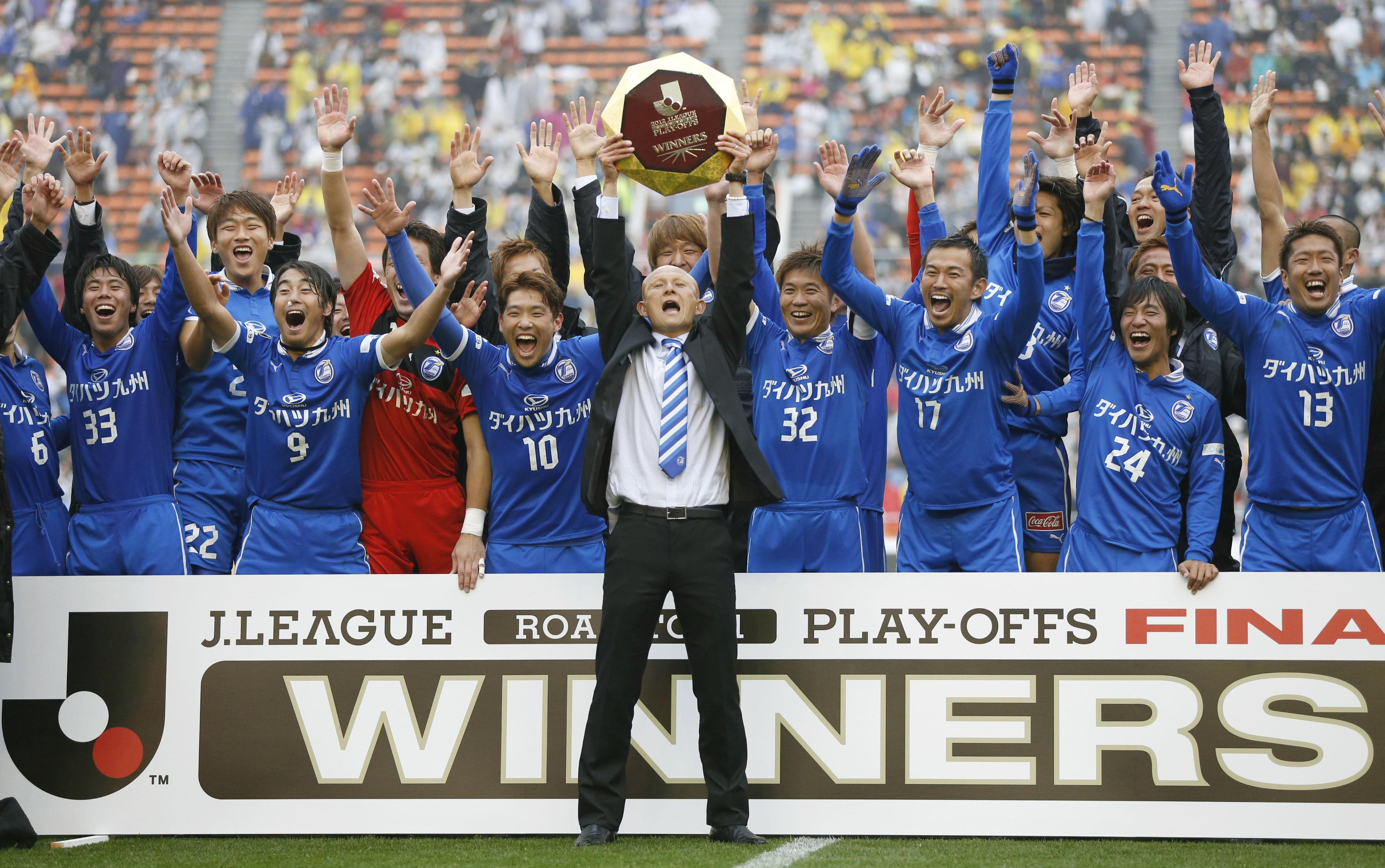 Moving on up: Oita Trinita manager Kazuaki Tasaka celebrates with his players after their 1-0 win over JEF United Chiba in the promotion playoffs final on Thursday at National Stadium. | KYODO