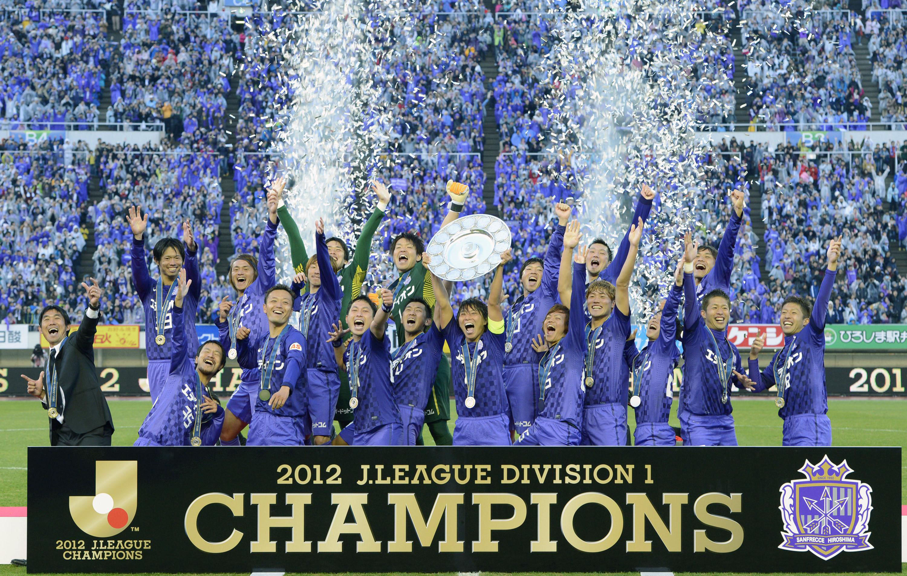 Purple haze: Sanfrecce Hiroshima lift the J. League championship trophy on Saturday at Big Arch in Hiroshima. | KYODO
